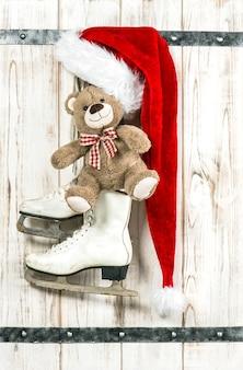 Décoration de noël de style vintage. bonnet rouge du père noël, ours en peluche et patins à glace blancs