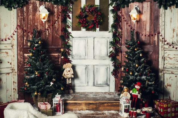 Décoration de noël vintage de la porte d'entrée avec des cadeaux et des lumières