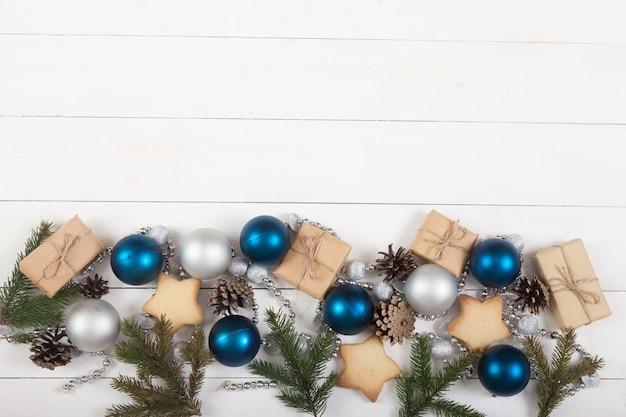 Décoration de nouvel an et de noël faite de branches de sapin, de cônes, de perles, de paillettes et de boules bleues et argentées sur blanc