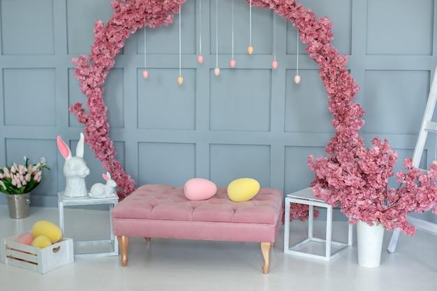 Décoration de pâques du salon. intérieur de la maison avec une grande couronne de sakura en fleurs de canapé rose sur le mur