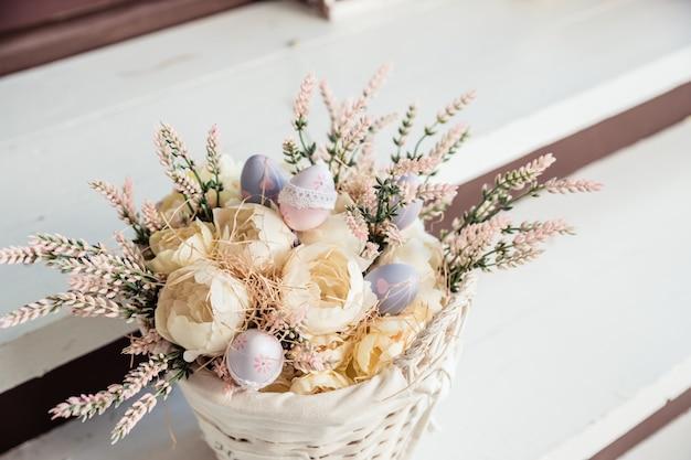 Décoration de pâques festive, plantes sèches, fleurs dans un panier sur table en bois. cadeau fait à la main pour les vacances,