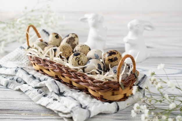 Décoration de pâques joyeuses fêtes avec des œufs de caille dans un panier et des lapins en céramique