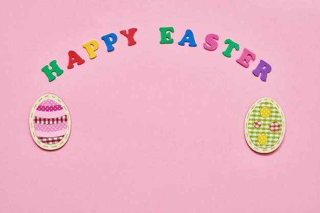Décoration de pâques et lettres colorées formant des mots bonne pâques sur rose