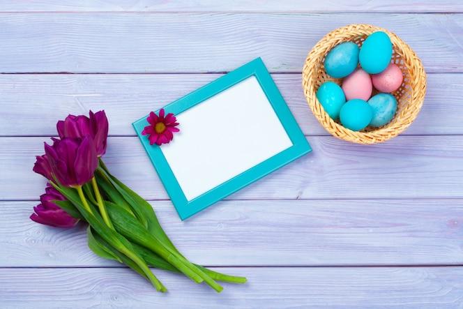 Décoration de pâques avec des tulipes, des œufs et un cadre vide. vue de dessus