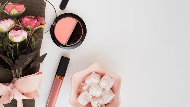 Décoration plate laïque avec des produits de maquillage sur fond blanc