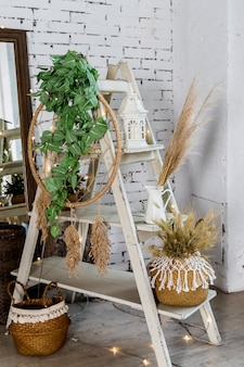 Décoration pour maison confortable faite avec des herbes sèches, lanterne, bougies et guirlandes sur mur de briques. fleurs séchées et végétation dans un intérieur moderne. décoration intérieure éco-style