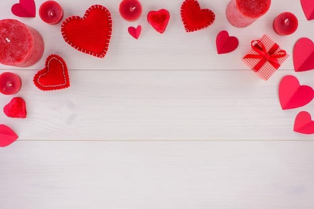 Décoration romantique saint valentin avec des coeurs et des bougies sur une table en bois blanche.