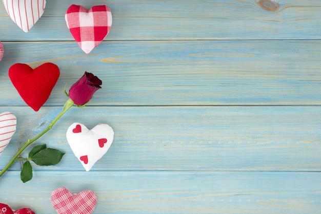 Décoration romantique saint valentin avec des roses et des coeurs sur une table en bois bleue.