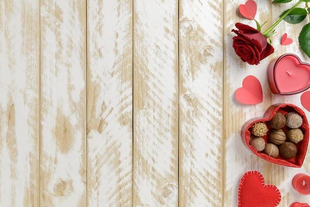 Décoration romantique saint valentin avec des roses et du chocolat sur un fond de table en bois blanc