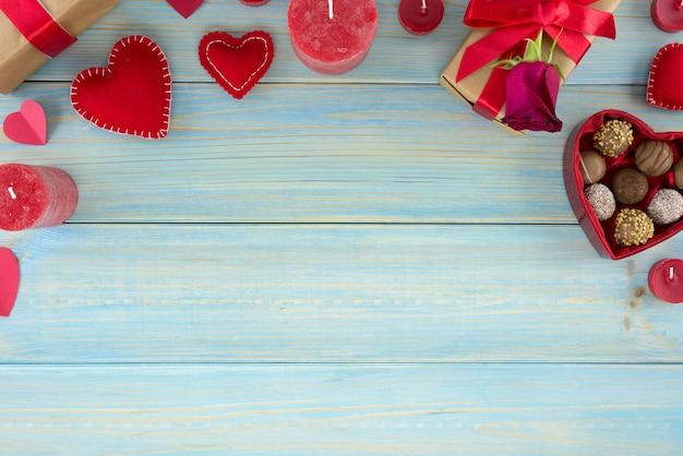 Décoration romantique saint valentin avec des roses et du chocolat sur une table en bois bleue.