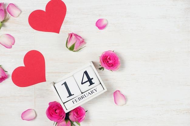 Décoration de la saint-valentin avec fleurs roses et bloc de calendrier 14 février sur bois. vue de dessus avec espace de copie