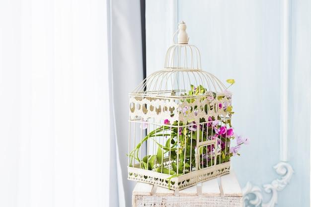 Décoration shabby chic avec une belle cage à oiseaux vintage et des fleurs