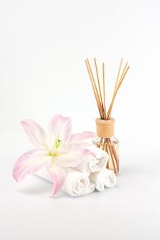 Décoration de spa avec lys rose, serviettes blanches et huile aromatique