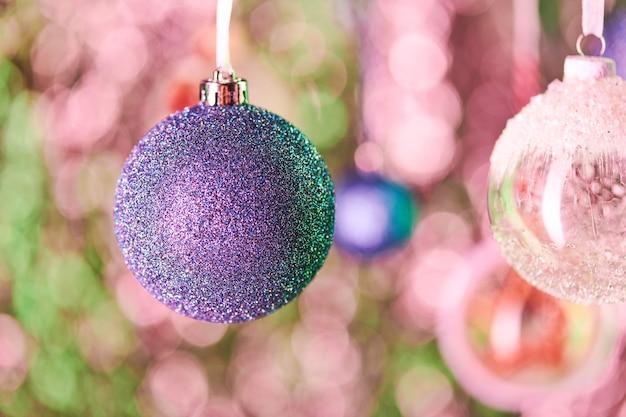 Décoration sphérique bleue recouverte de minuscules paillettes argentées et autres boules décoratives suspendues devant la caméra sur fond de noël coloré