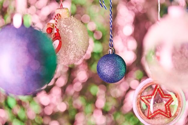 Décoration sphérique bleue recouverte de minuscules paillettes et d'autres jolies boules décoratives suspendues devant la caméra sur fond de noël coloré