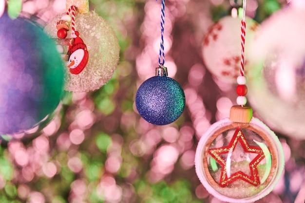 Décoration sphérique bleue recouverte de minuscules paillettes, boules décoratives avec neige artificielle et étoile suspendue devant la caméra sur fond coloré