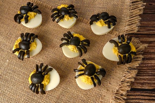 Décoration de table halloween. araignées faites d'œufs et d'olives. collation de fête. sur un sac.