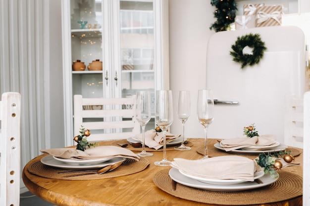Décoration de table de noël dans la cuisine, table de banquet avec verres avant de servir la nourriture, gros plan de la table du dîner de noël avec décorations saisonnières, verres en cristal et cerf décoratif