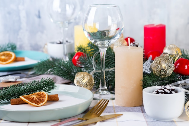 Décoration de table de noël et du nouvel an avec orange sec et cannelle sur un textile gris. salle à manger décorée de pommes de pin, de branches et de bougies