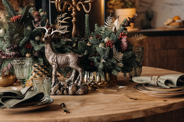 Décoration de table de noël, table de banquet avec des verres avant de servir la nourriture, gros plan sur la table du dîner de noël avec des décorations saisonnières, des verres en cristal et des cerfs décoratifs