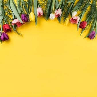 Décoration de tulipes colorées sur fond jaune avec un espace pour l'écriture du texte