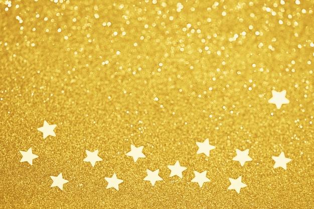 Décoration de vacances de paillettes confettis étoiles d'or, lumières bokeh défocalisés