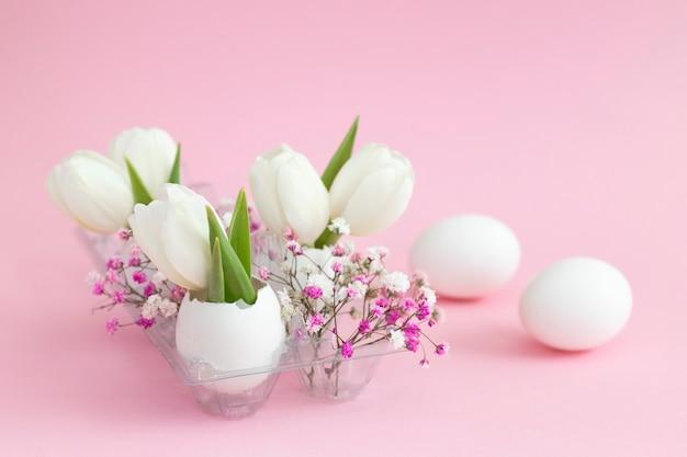 Décoration de vacances de pâques en tulipes blanches coquille d'oeuf et gypsophile rose et deux oeufs blancs sur fond pastel rose. copie espace.