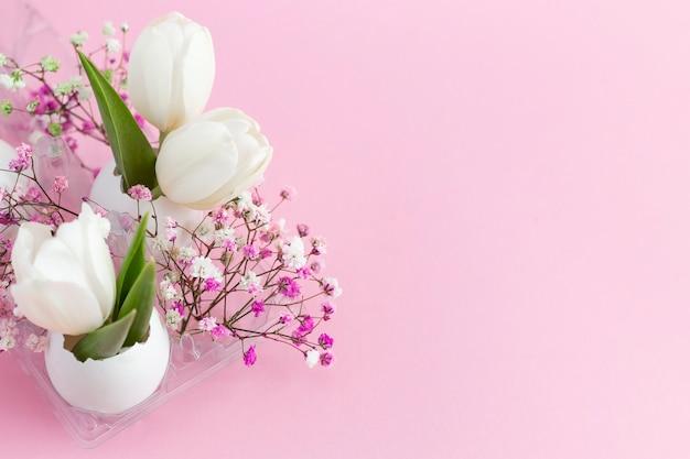 Décoration de vacances de pâques en tulipes blanches coquille d'œuf et gypsophile rose sur fond pastel rose. copie espace.