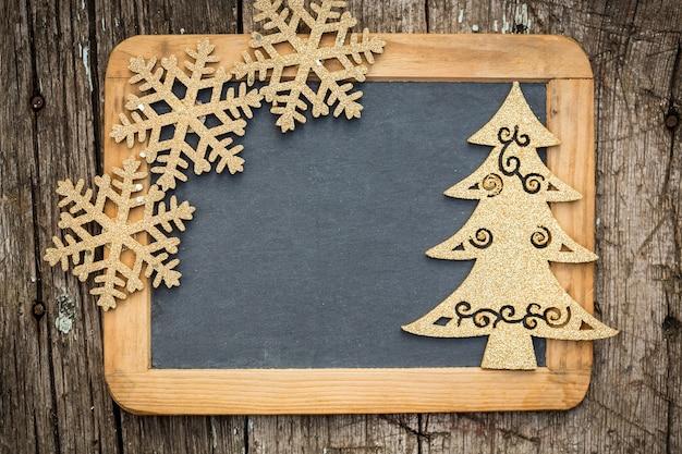 Décorations d'arbre de noël d'or sur tableau noir en bois vintage avec espace de copie. carte de vacances de noël