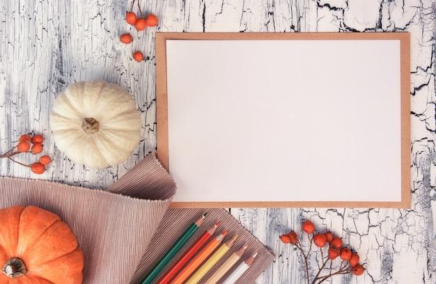 Décorations d'automne, crayons sur une table rustique avec une feuille de papier vierge, vue de dessus