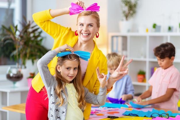 Décorations sur les cheveux. professeur et écolière rayonnants et excités drôles mettant des décorations en papier sur leurs cheveux