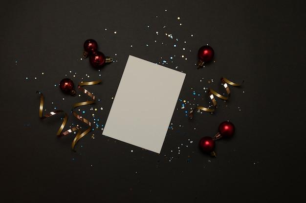 Décorations dorées de vacances et cahier blanc sur fond noir.
