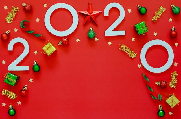 Décorations du nouvel an avec numéro de l'année et fond vide sur le rouge. appartement poser minime vacances.