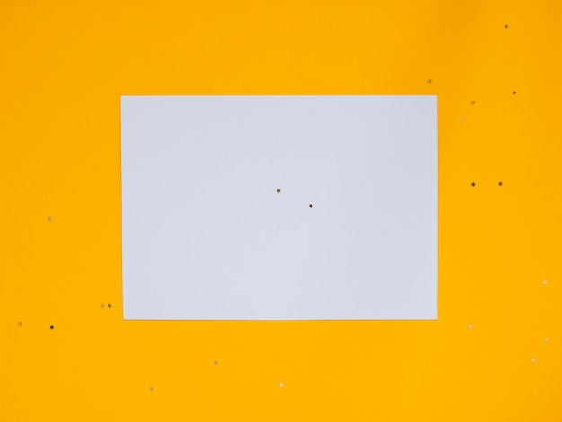 Décorations étoiles dorées de vacances et blanc propre blanc pour votre texte sur fond jaune