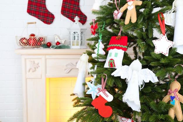 Décorations faites à la main de noël sur l'arbre de noël sur le fond intérieur clair de maison