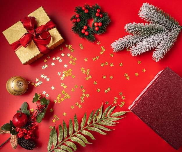 Décorations festives de noël et du nouvel an avec boîte-cadeau, boules, cônes et jouets sur fond rouge.