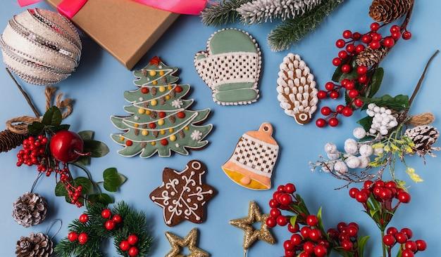 Décorations festives de noël et du nouvel an avec coffrets cadeaux, boules, cônes, pain d'épice sur fond bleu.