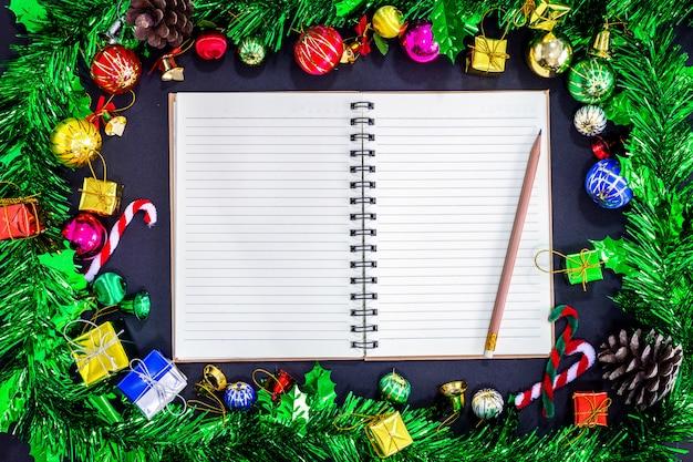 Décorations de fête de noël avec bloc-notes vide et un crayon sur fond de papier noir, ne