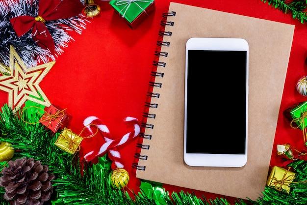 Décorations de fête de noël avec smartphone vide, cahier et un crayon sur backg de papier rouge