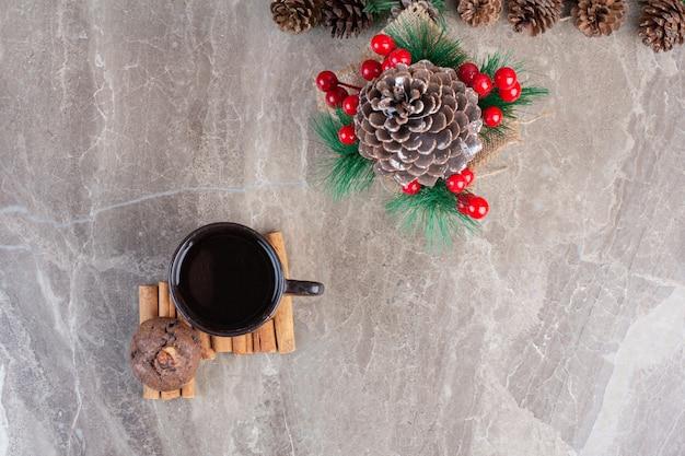Décorations de fête avec des pommes de pin à côté d'une tasse de thé sur des bâtons de cannelle et un biscuit sur du marbre.