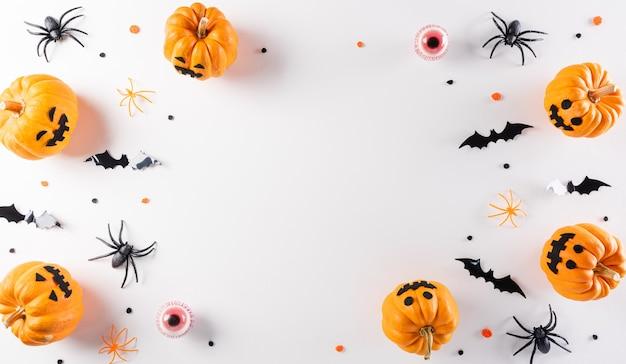 Décorations d'halloween faites de chauves-souris en papier citrouille et d'araignées noires sur fond blanc