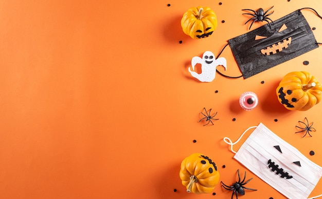 Décorations d'halloween faites de chauves-souris en papier citrouille et d'araignées noires sur fond orange