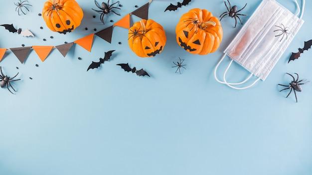 Décorations d'halloween faites de citrouille, chauves-souris en papier et masque chirurgical sur fond bleu pastel. mise à plat, vue de dessus de la célébration d'halloween pendant la situation de pandémie de covid-19.