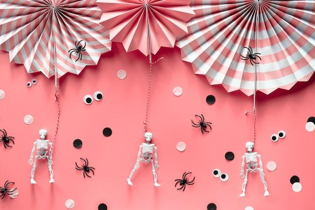 Décorations d'halloween roses. éventails en papier décoratif, araignées, squelettes humains et yeux écarquillés.