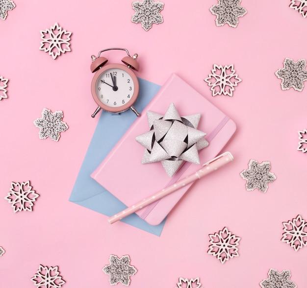 Décorations d'hiver de noël, cahier d'affaires avec réveil, flocons de neige et archet sur fond rose.