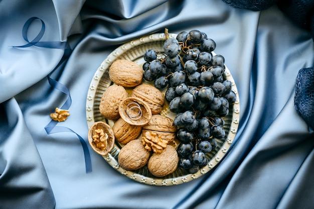 Décorations de mariage avec des raisins et des noix dans une assiette sur fond de tissu bleu, vue de dessus.
