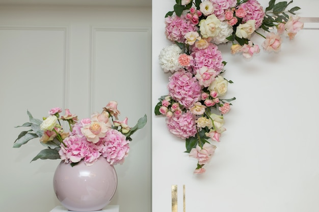 Décorations de mariage. vase de décoration de vacances avec des fleurs fraîches près de l'arc de mariage. roses roses et oeillets