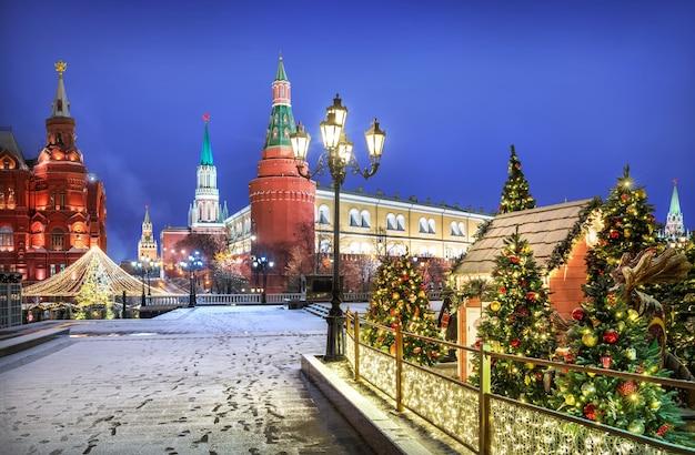 Décorations de noël sur les arbres de noël sur la place manezhnaya à moscou près du kremlin sur une nuit d'hiver enneigée