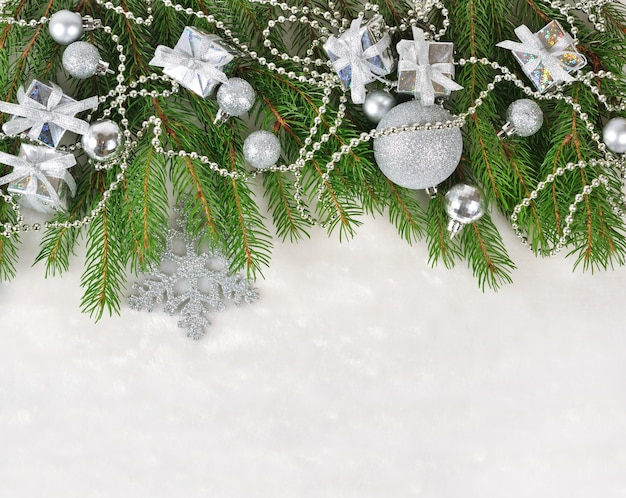 Décorations de noël en argent sur une branche d'épinette sur fond blanc