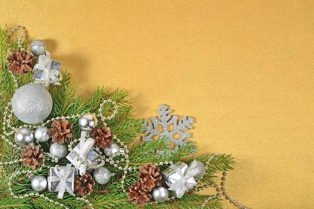 Décorations de noël en argent sur une branche d'épinette sur fond doré